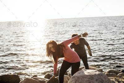 Playful young couple walking on rocks against sea