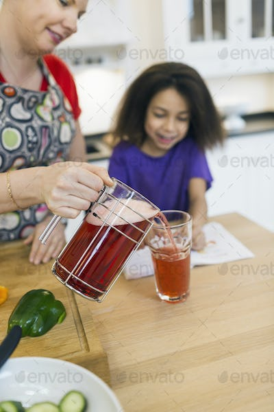 Mother serving glass of juice to daughter in kitchen