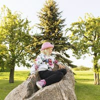 Side view of girl sitting on rock at field