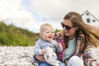 Happy mother with son sitting on beach