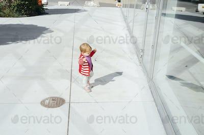 Full length of baby girl standing outside glass building