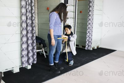 Fashion designer measuring woman's thigh in jeans factory