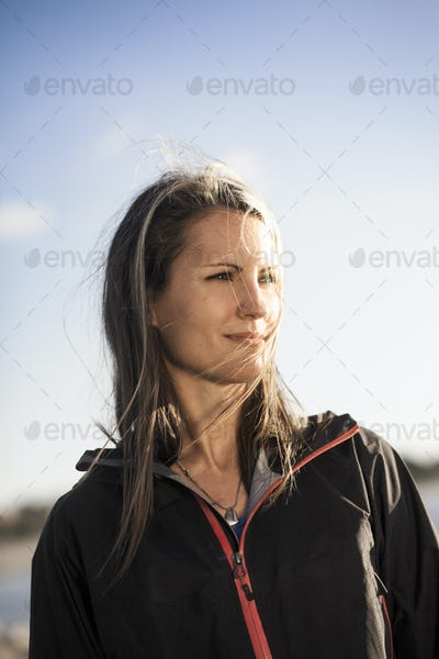Thoughtful young woman in jacket standing against sky on sunny day