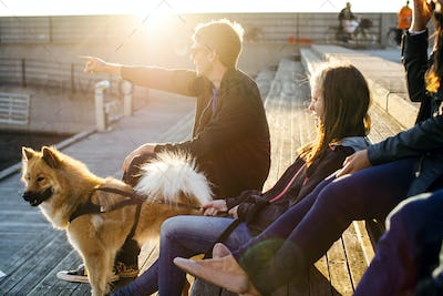 Man with dog showing something to friends while relaxing on steps outdoors