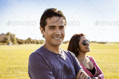 Portrait of happy man with girlfriend at park against sky
