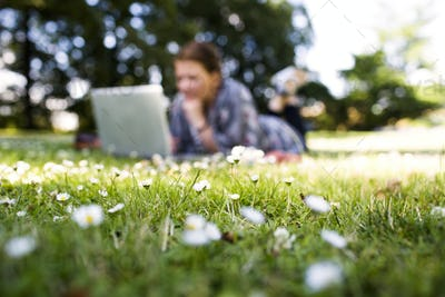 Freelancer using laptop while lying on grass at park
