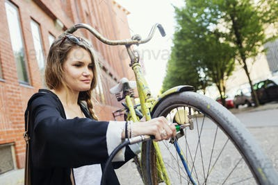 Young woman inflating bicycle tire on sidewalk