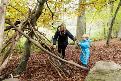 Mother and son making wooden tent in forest