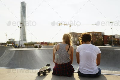 Rear view of female friends sitting at edge of skateboard ramp