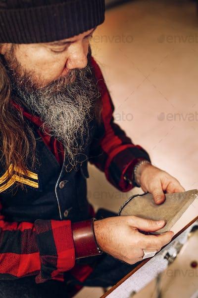 Male worker checking bag pocket in workshop