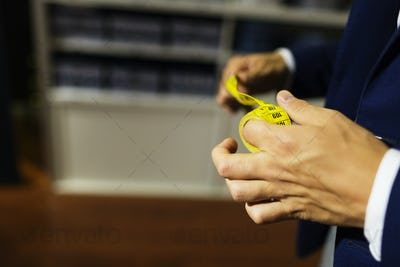 Cropped image of designer holding rolled up tape measure in clothing store
