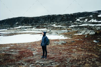 Full length of young man in warm clothing standing on mountain landscape