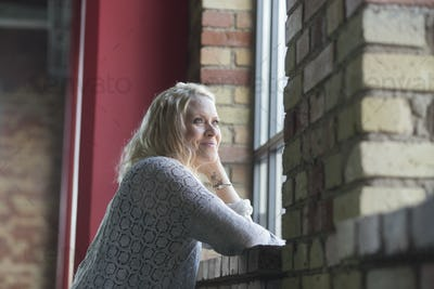 Side view of thoughtful young woman standing by window at gym
