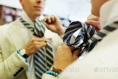 Cropped image of customer tying necktie in front of mirror at store