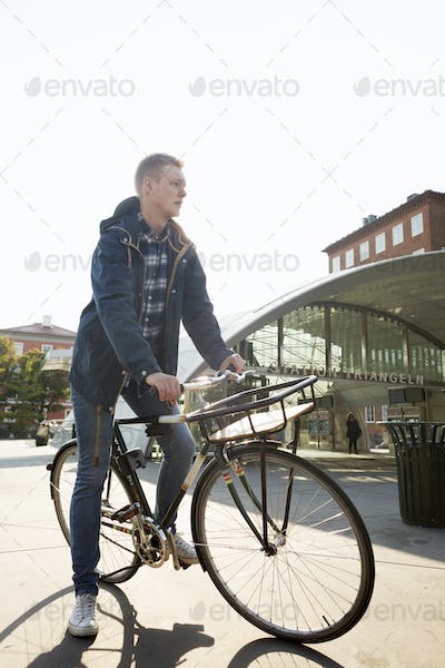 Full length of businessman riding bicycle outside railway station