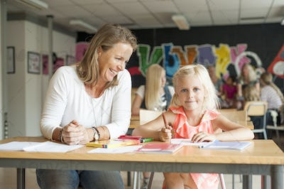 Happy teacher watching girl drawing with color pencil in classroom