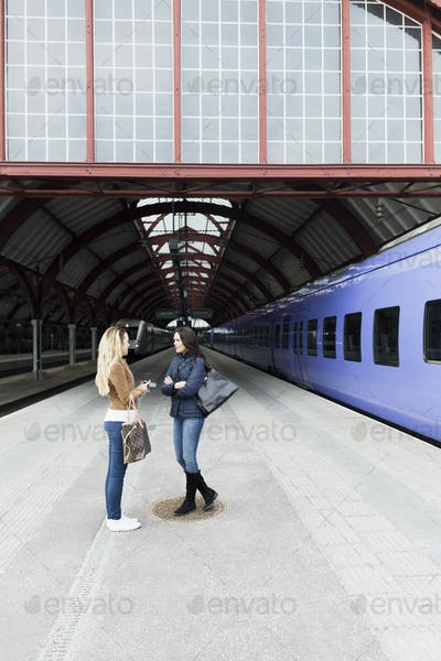 Female friends standing together at railroad station