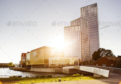 Sunlight streaming through modern buildings by canal