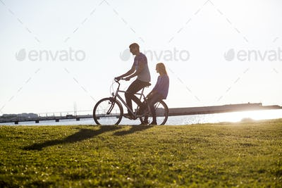 Couple riding bicycle on grassy landscape by sea against clear sky