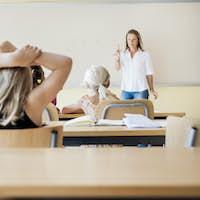 Female teacher teaching class in front of whiteboard
