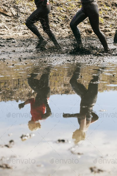 Low section of women running through muddy puddle