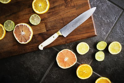 Directly above shot of sliced citrus fruits and knife on chopping board