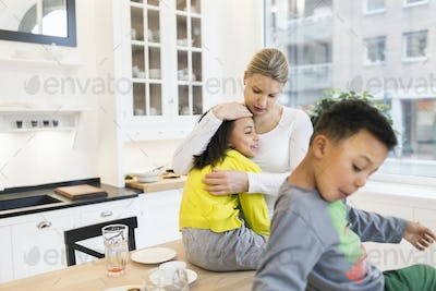 Mother hugging daughter with boy in foreground at kitchen