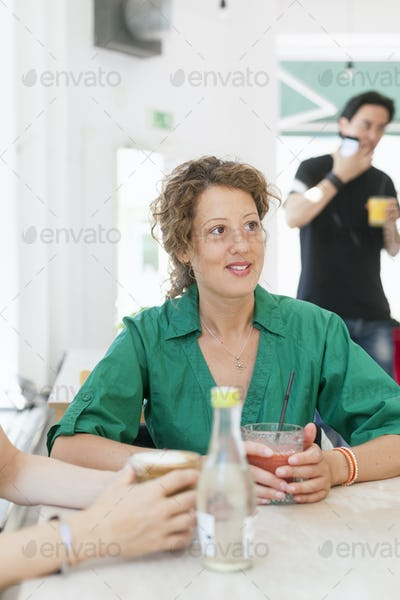 Mid adult woman with friend at cafe table