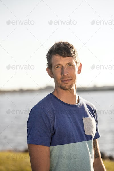 Portrait of confident man standing by sea against clear sky