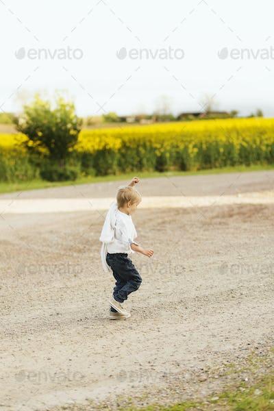 Full length of playful boy walking on dirt road by oilseed rape field