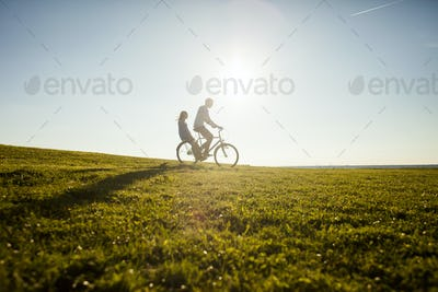 Couple riding bicycle on grassy landscape against clear sky