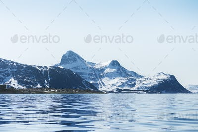 Scenic view of sea by snowcapped mountains against clear sky
