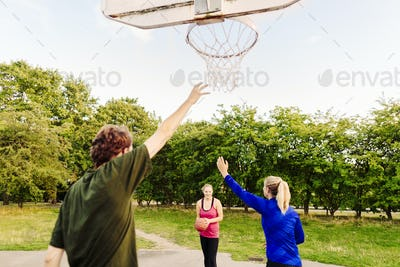 Friends playing basketball at park