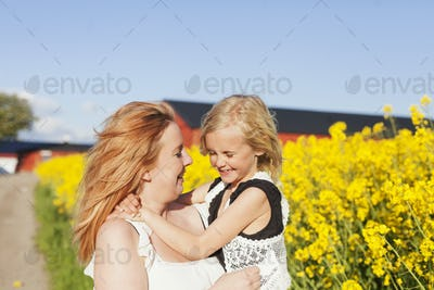 Happy woman carrying daughter at oilseed rape field