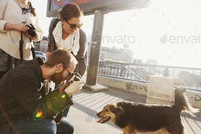 Friends photographing dog on bridge in city