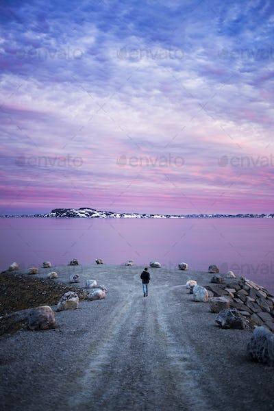 Rear view of man walking on groyne leading towards sea during sunset