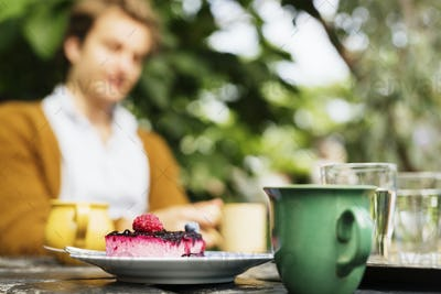 Cake and coffee on table with man sitting in background