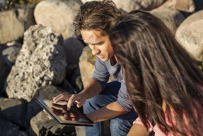 Young couple using digital tablet on rocks