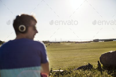Rear view of man listening music at park against clear sky