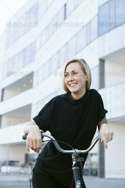 Smiling college student with bicycle against building