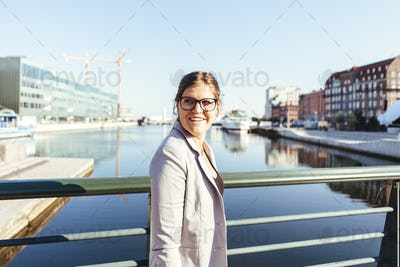 Smiling businesswoman looking away while standing on bridge in city