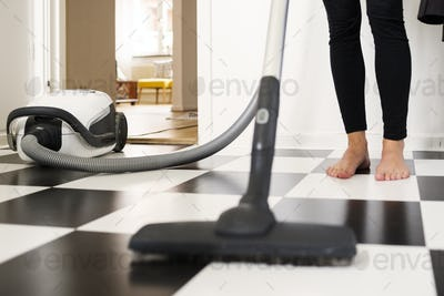 Low section of woman cleaning floor with vacuum cleaner