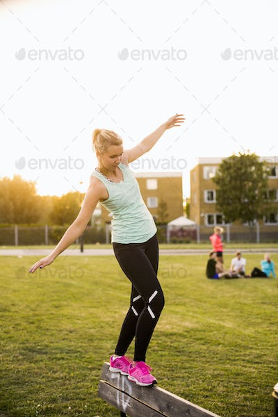 Sporty woman balancing while walking on bench at park during sunset