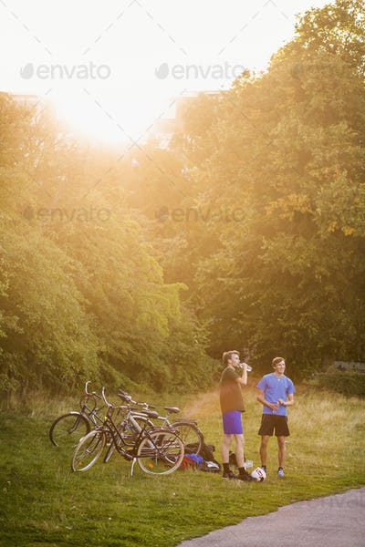 Sporty male friends standing by bicycles at park during sunset