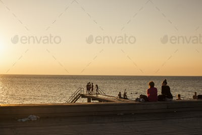 People relaxing on pier in front of sea during sunset