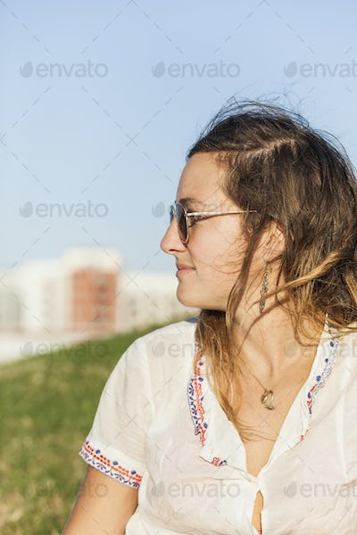 Mid adult woman wearing sunglasses while looking away in park