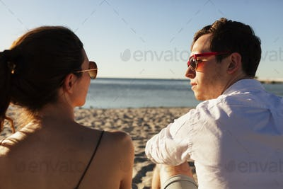 Rear view of man and woman talking while relaxing at beach