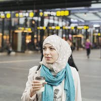 Woman looking away while holding coffee cup at railroad station