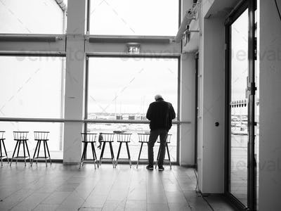 Rear view of man standing in front of window in office building