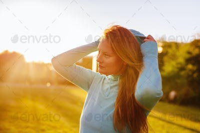 Young sporty woman wearing hooded jacket at park during sunset